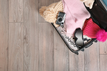 Open suitcase with warm clothes, photo camera and ski goggles on wooden floor. Winter vacation concept