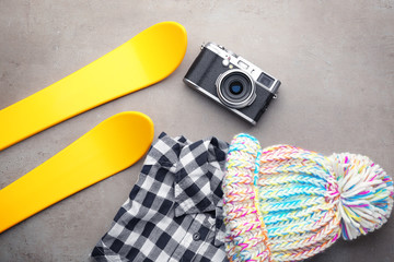 Warm clothes with photo camera and skis on grey background. Winter vacation concept