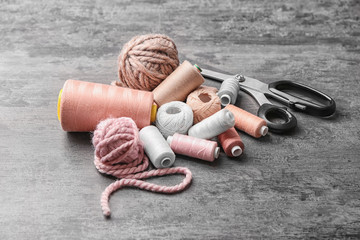 Different types of threads with scissors on grey background