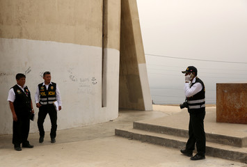 Policemen investigate near the statue of 'Christ of the Pacific' that was partially burned after a fire at the base of the monument, at Morro Solar hill in Chorrillos