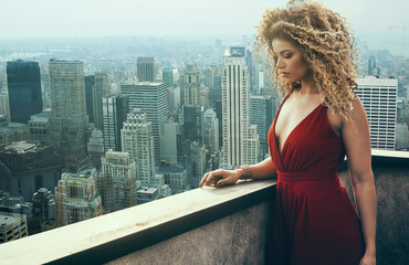 Beautiful and pensive woman portrait wearing red dress and New York cityscape