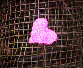 Colorful decorative heart on old rustic iron sieve background. conceptual photo.