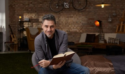 Happy older white man reading book at home