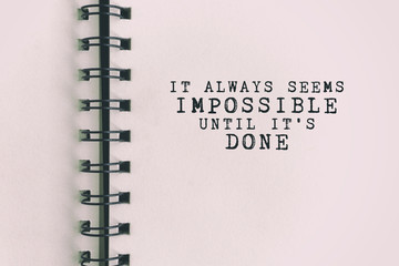 Inspirational Quote - It always seems impossible until it's done. Blurry retro background.