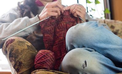 Woman knitting on an armchair