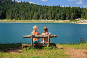 rear view of two girls sitting on a bench near the lake in the mountains