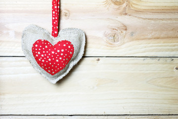 Heart from material on wooden background, free space for text. Valentine's Day.