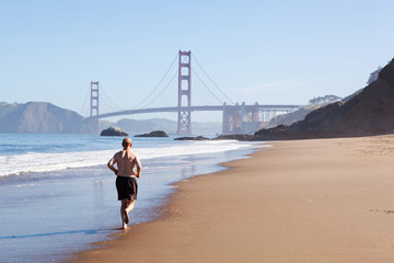 Old man running on baker beach close to Golden Gate bridge.