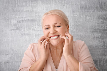Portrait of smiling mature woman on grey background