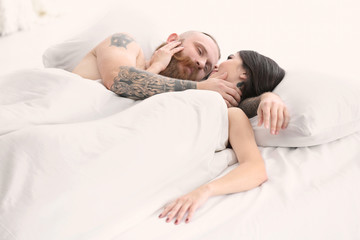 Attractive young couple with tattoos in bed at home