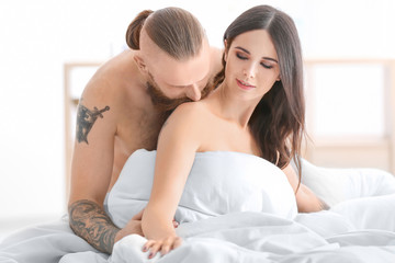 Tattooed man with his girlfriend in bed at home