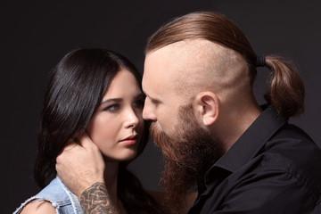 Tattooed man with his girlfriend on dark background