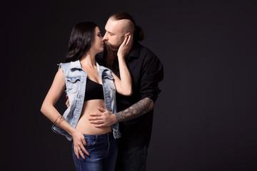 Tattooed man kissing his girlfriend on dark background