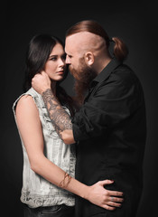 Tattooed man with his girlfriend on dark background
