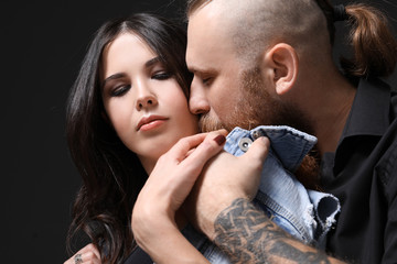 Tattooed man kissing his girlfriend on dark background