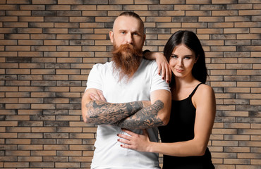 Tattooed man with his girlfriend on brick wall background