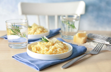 Plate with delicious risotto on wooden table