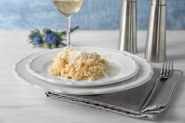 Plate with delicious risotto on table