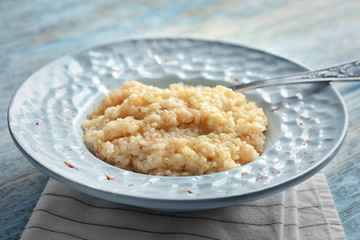Dish with delicious risotto on wooden table