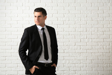 Handsome man in elegant suit near white brick wall