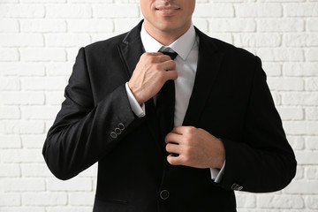 Handsome man in elegant suit near white brick wall, closeup