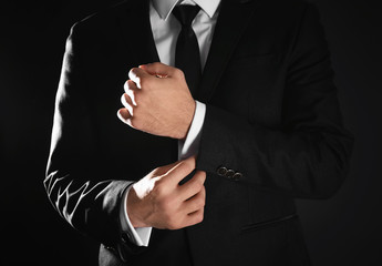 Handsome man in elegant suit on black background, closeup