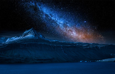 Volcanic mountain and milky way over fjord at night, Iceland