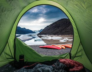 Camp by glacial lake in the mountains with kayak, Iceland