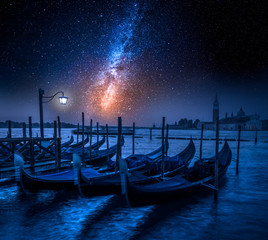 Swinging gondolas in Venice at night with stars