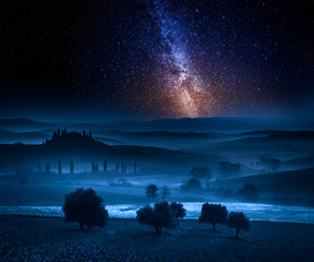 Milky way over fields in the valley in Tuscany, Italy