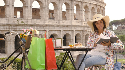 Young woman tourist reads a book sitting at the table outside a bar restaurant in front of the Colosseum in Rome with coffee, juice and cornetto. Elegant beautiful dress with large hat and colorful