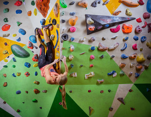 Young woman bouldering in climbing gym, hanging in upside down position