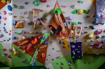 Young woman bouldering on overhanging wall in climbing gym