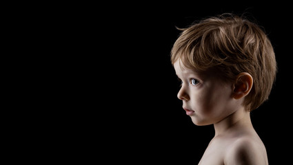 Profile portrait of four-year old boy over black