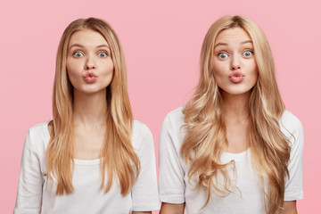 Horizotal shot of two attractive sisters dressed in white casual blouses, pout lips and make grimace, isolated over pink background. Females with appealing look model in studio. Beauty concept