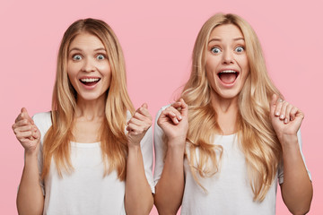 Excited overjoyed female students clench fists, being very emotional while hear results of exam, stand next to each other, isolated over pink background. Amazed beautiful women being in high spirit