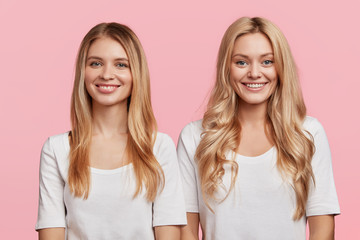 Horizontal shot of beautiful female with cheerful expressions rejoice good starting of day, stand close to each other, have shining smile, demonstrate perfect teeth, isolated over pink background