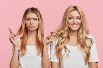 Envious young female compares her hair with friend, wants to have curls, discuss something, express different emotions, pose against pink background. Youth, friendship and relationship concept