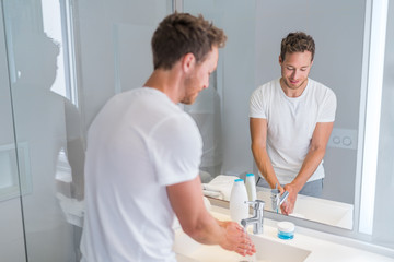 Young man washing hands at home cleaning hand under running water in bathroom sink. House, aparment condo luxury living lifestyle.
