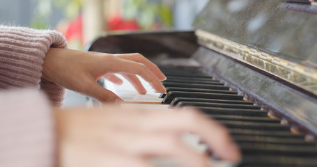 Female hand playing piano