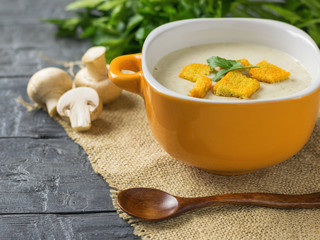 Freshly prepared cream soup of mushrooms with croutons and herbs and wooden spoon on a wooden table.