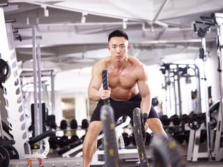asian bodybuilder exercising in gym using battle rope.