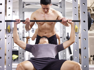 young asian man lifting weight in gym with help from trainer