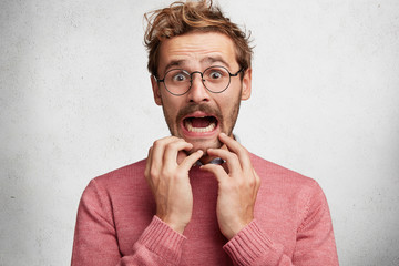 Worried scared fashionable man looks with terrified expression, keeps arms on chin, dressed in pink sweater, isolated over white background. Emotional bearded young guy receives unexpeted news Wall mural