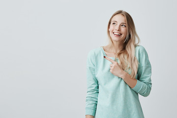 Pretty smiling joyfully female with fair hair, pointing her index fingers, showing copy space for advertising content. Studio shot of good-looking beautiful blonde girl isolated against studio wall.