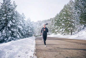 Young woman running in snowy area.