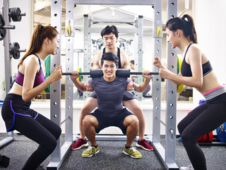 young asian man lifting weight in gym