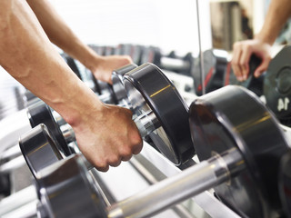 hand of a male lifting a dumbbell