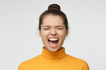 Closeup portrait of screaming with closed eyes crazy young woman in yellow sweater isolated on gray background