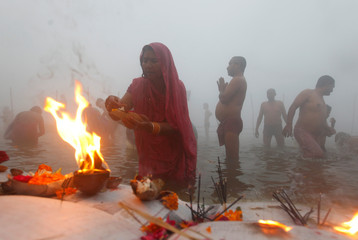 """Hindu devotees pray at Sangam, the confluence of the Ganges, Yamuna and Saraswati rivers, on a foggy winter morning on the occasion of """"Makar Sankranti"""" festival in Allahabad"""